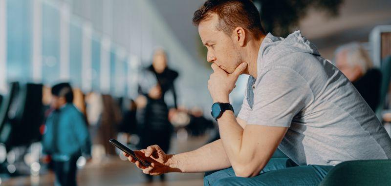 mies katsoo mietteissä kännykkää